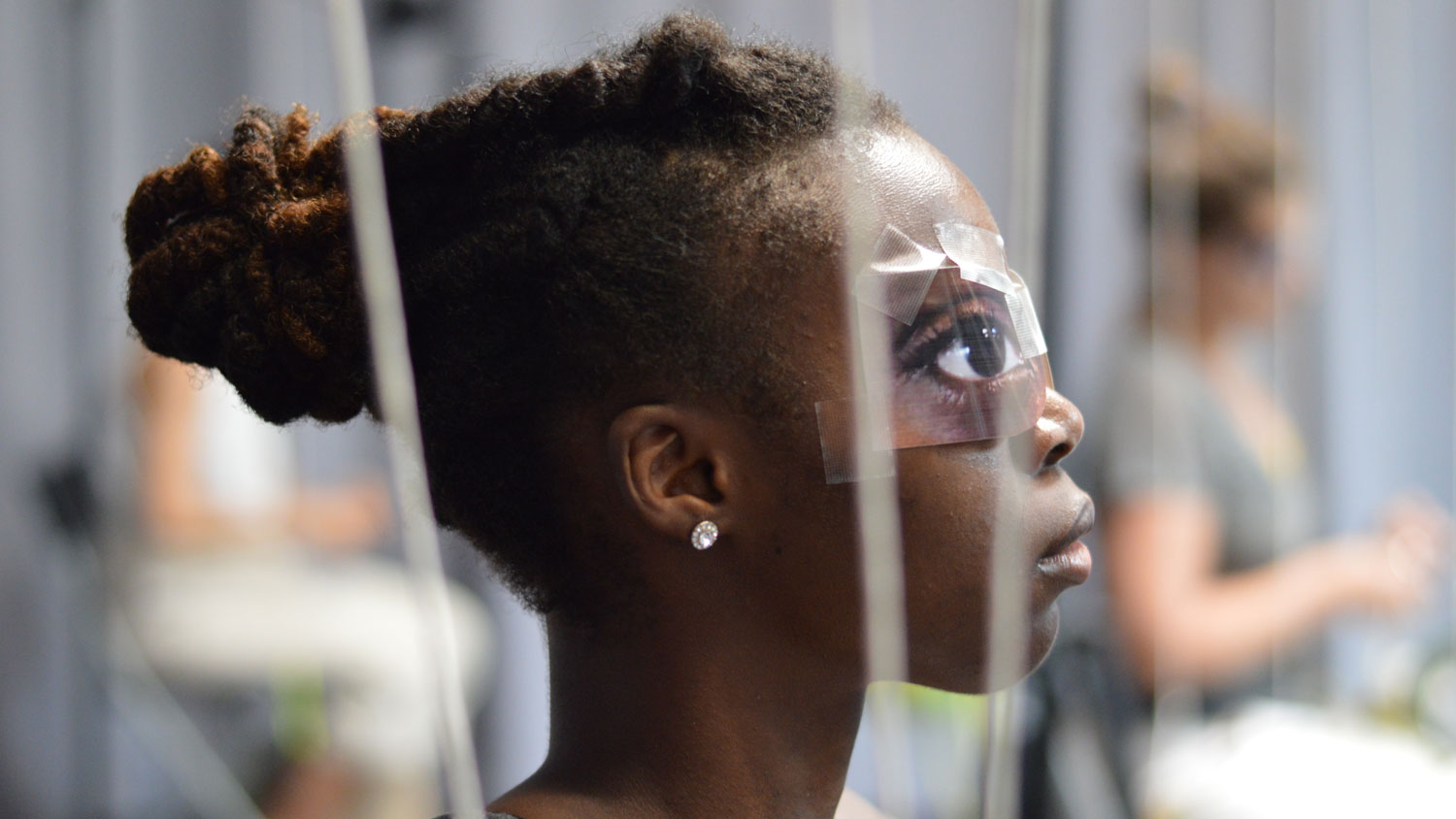 a young black womans head with paper eyes tapes over her eyes