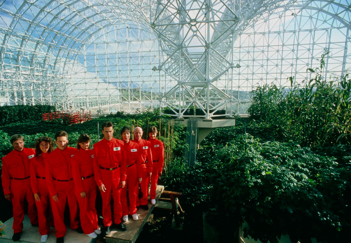 a group of biosphere participants in red jumpsuits inside the biosphere in a giant garden