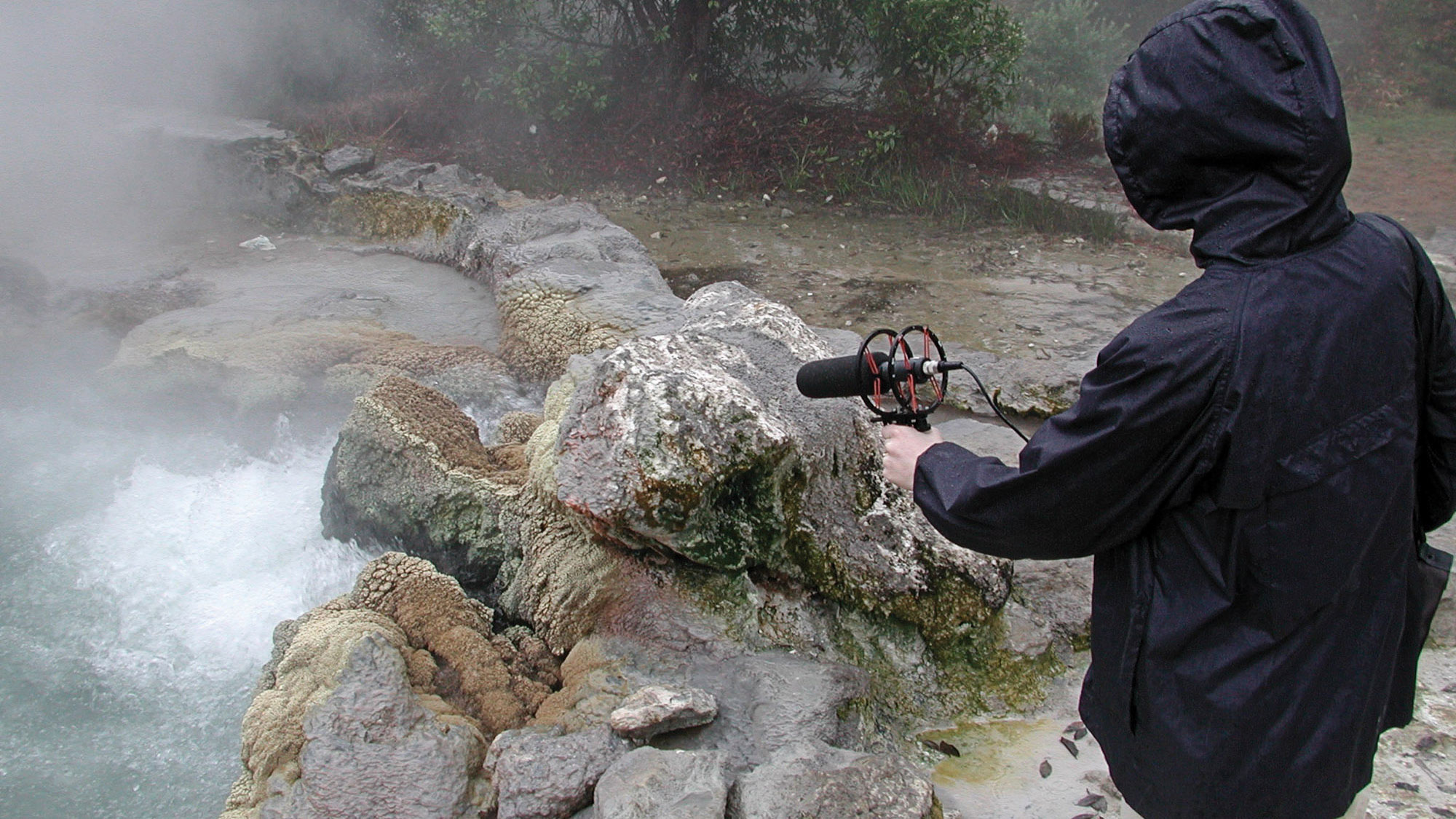 a person in a blue coat holding a microphone over some hot springs.