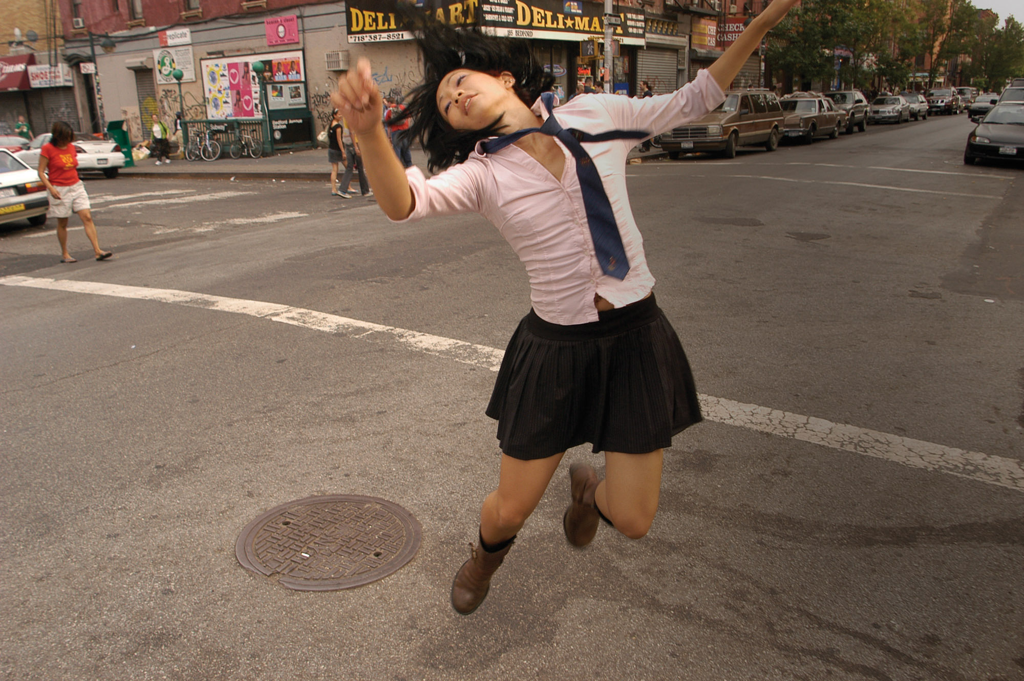 A Japanese school girl jumping in the street.