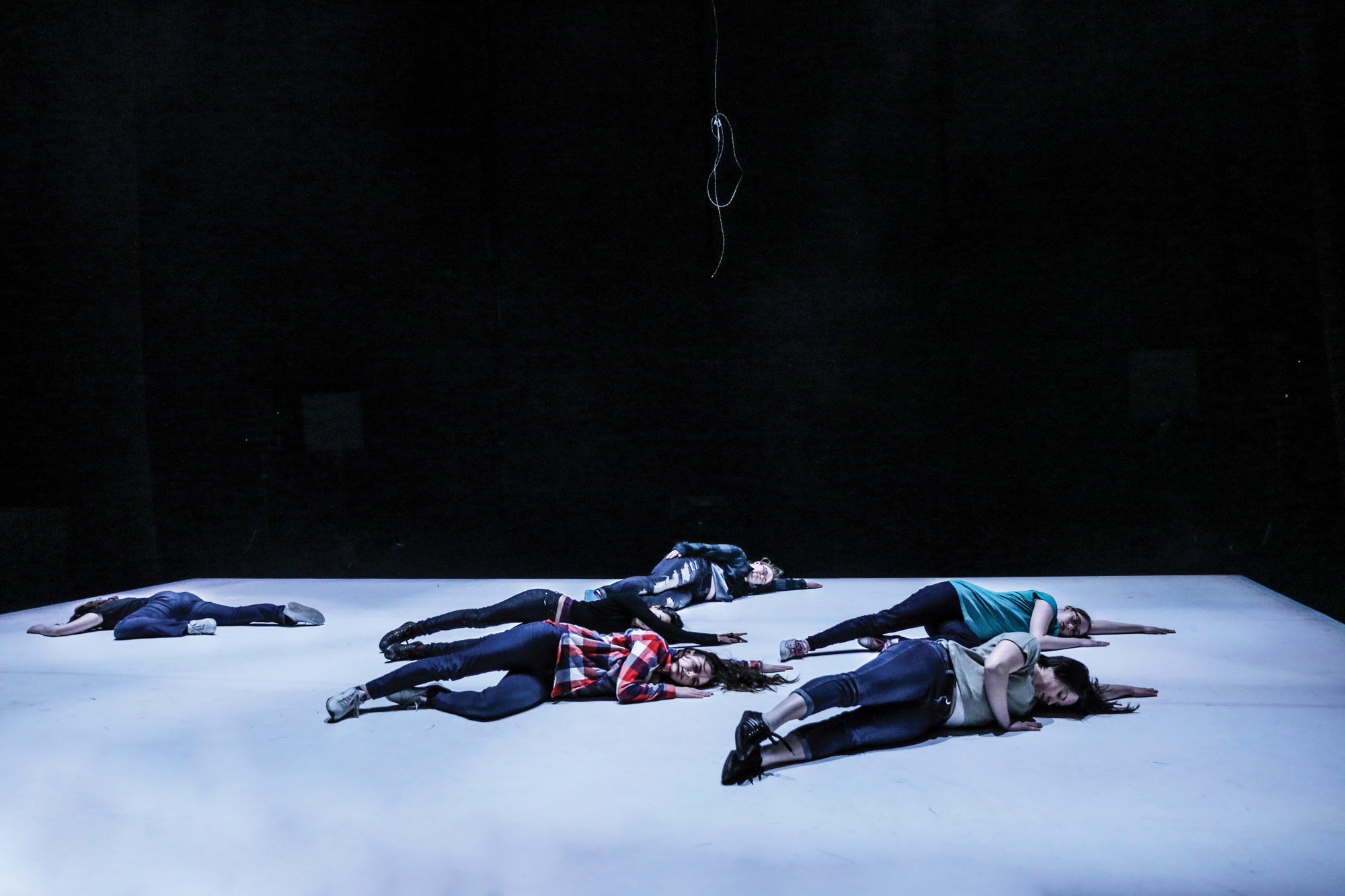 dancers laying on a white stage
