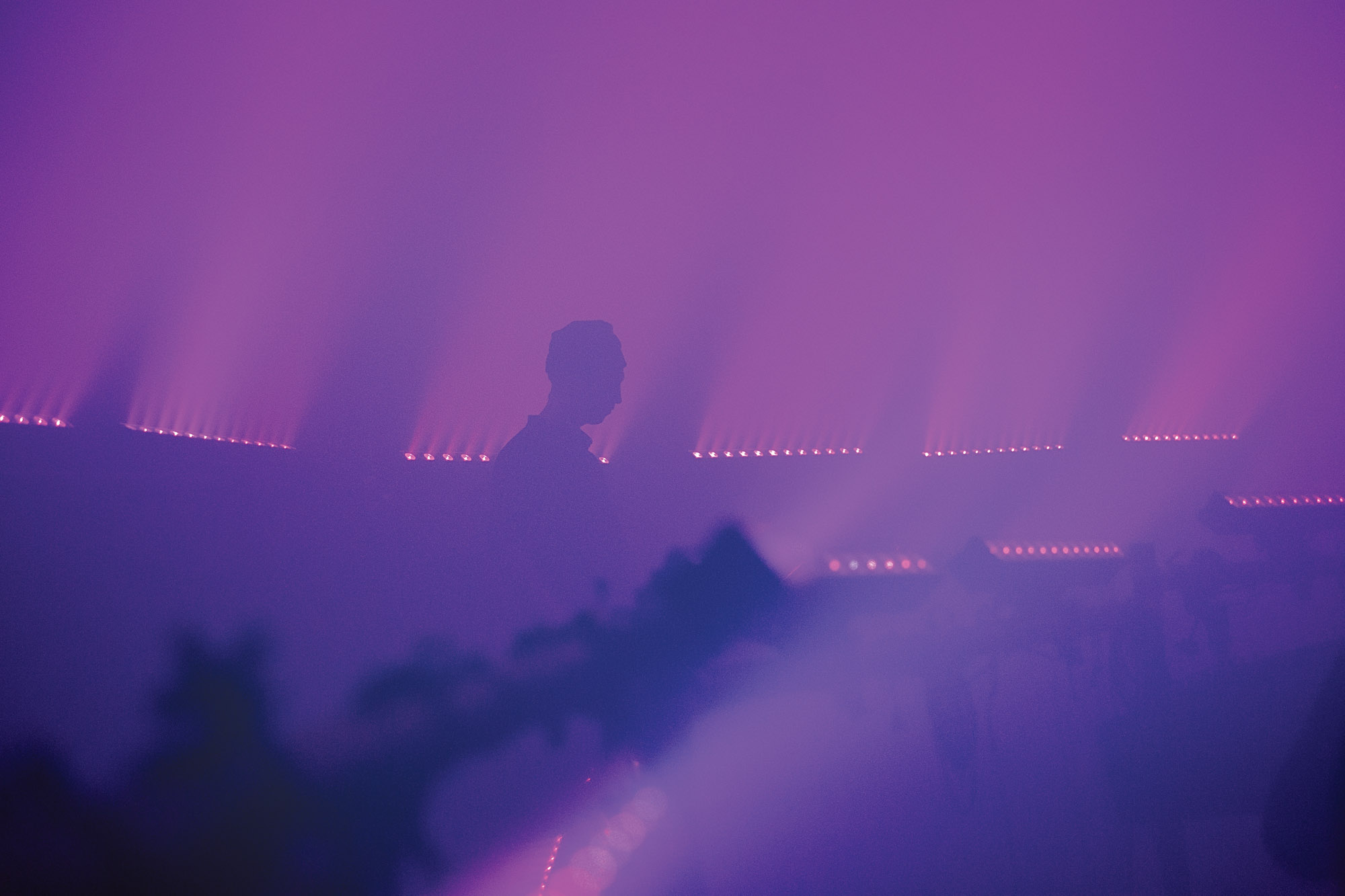 tim hecker's silouette in dense theatrical fog
