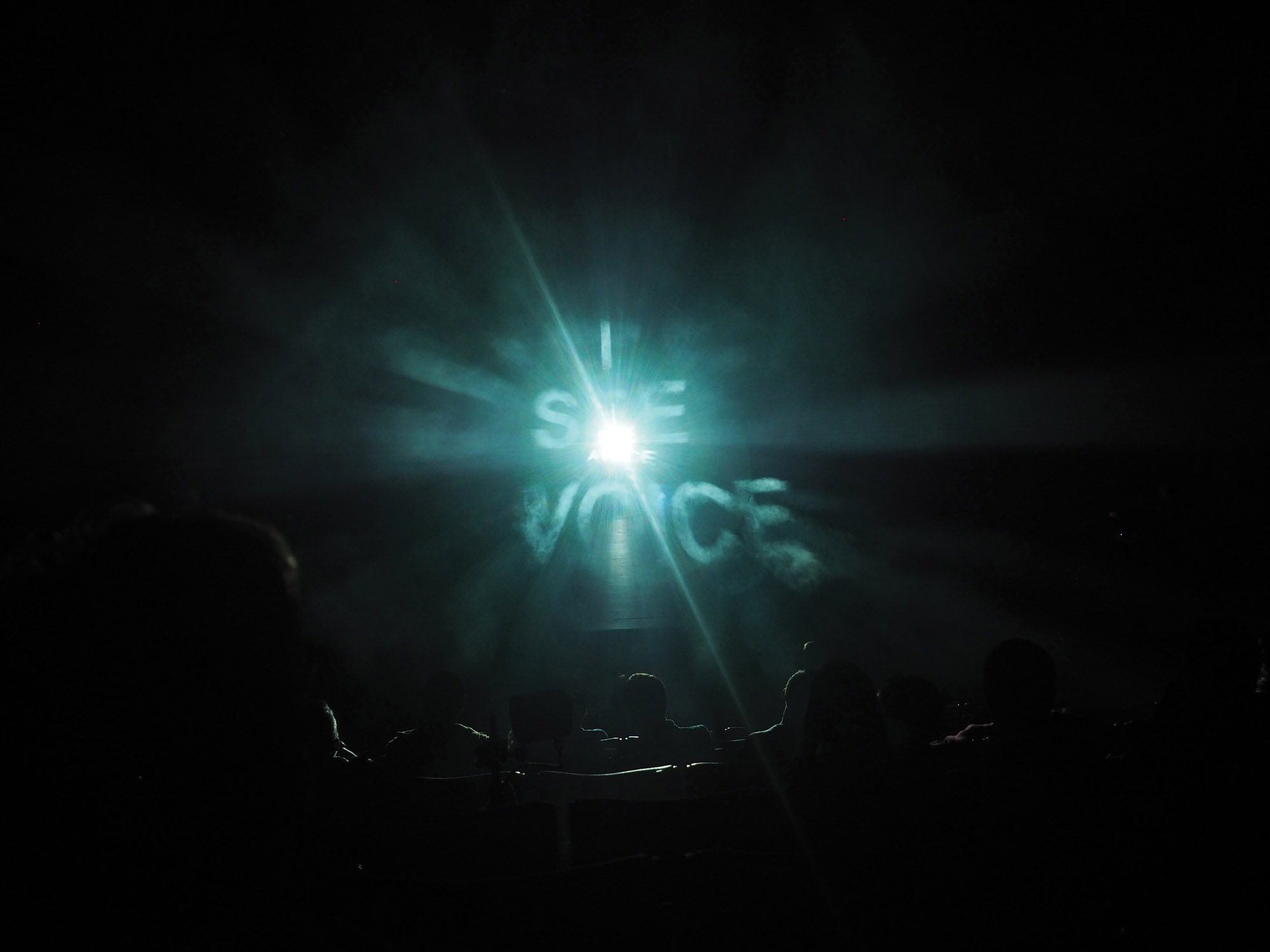 "ghostly theatrical fog illuminates projected words ""i see voice"" in the empac theater."