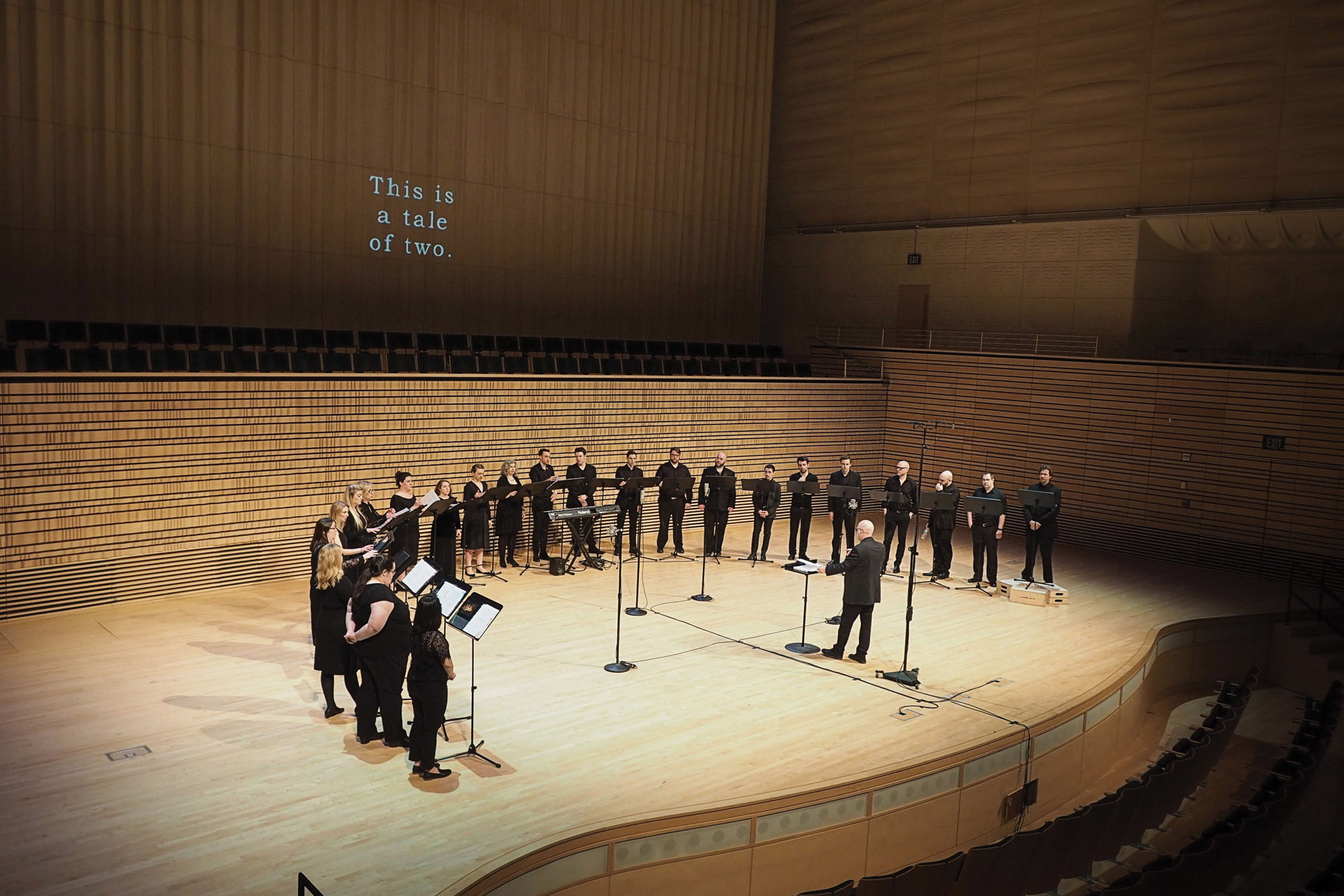 the crossing choir in front of a projection on the concert hall stage in 2018