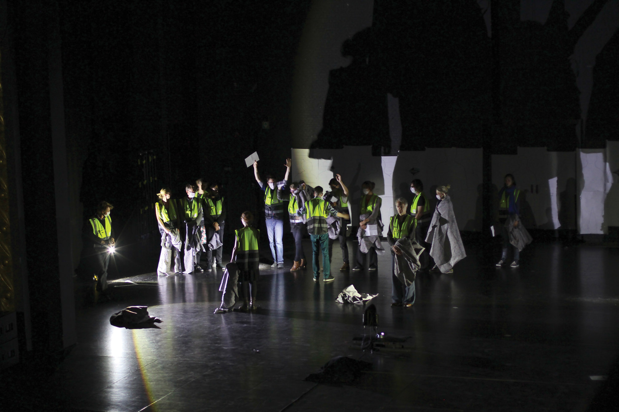 many people on the theater stage in construction vests