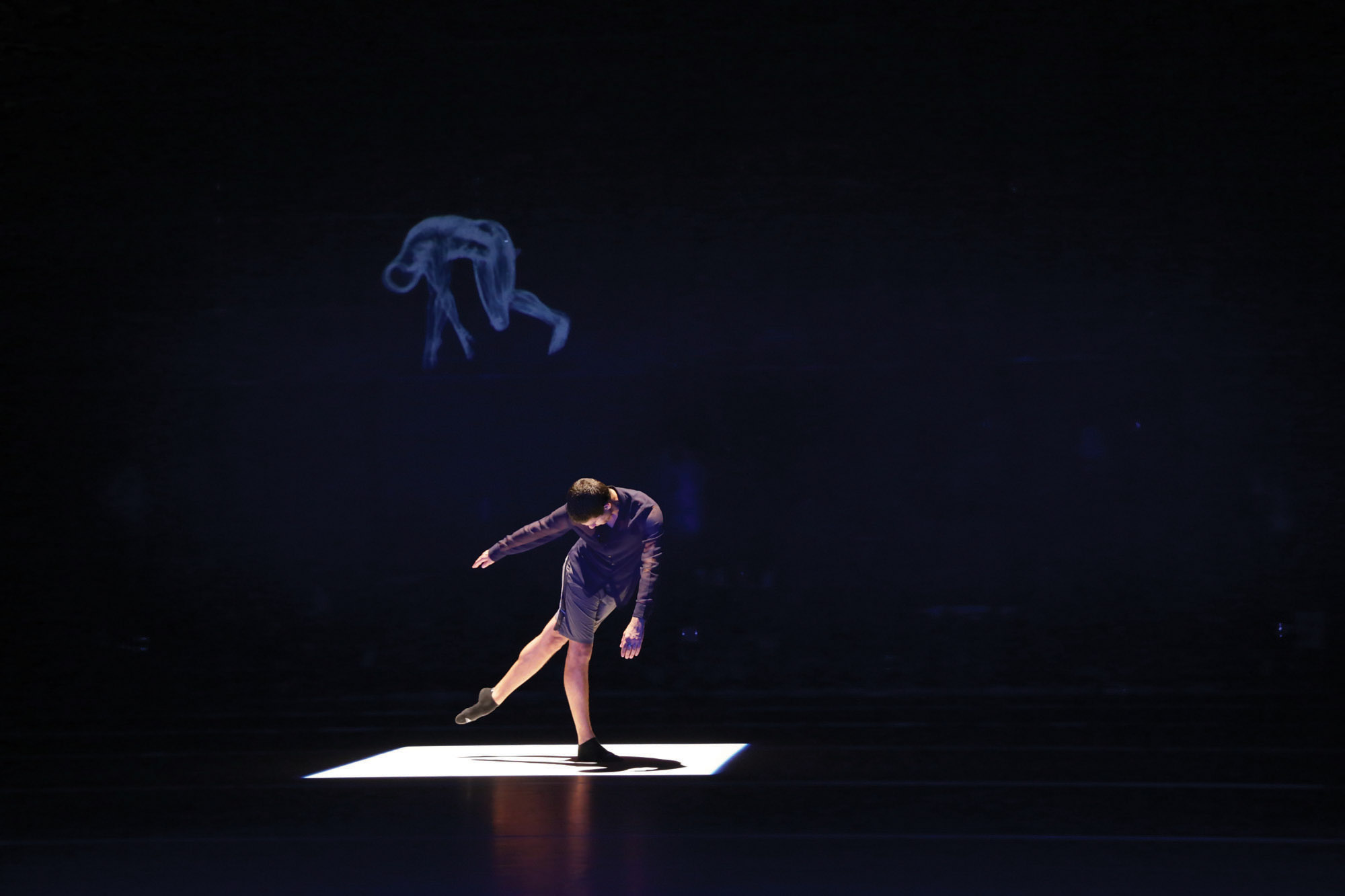 a dancer on a dark stage under a spotlight.