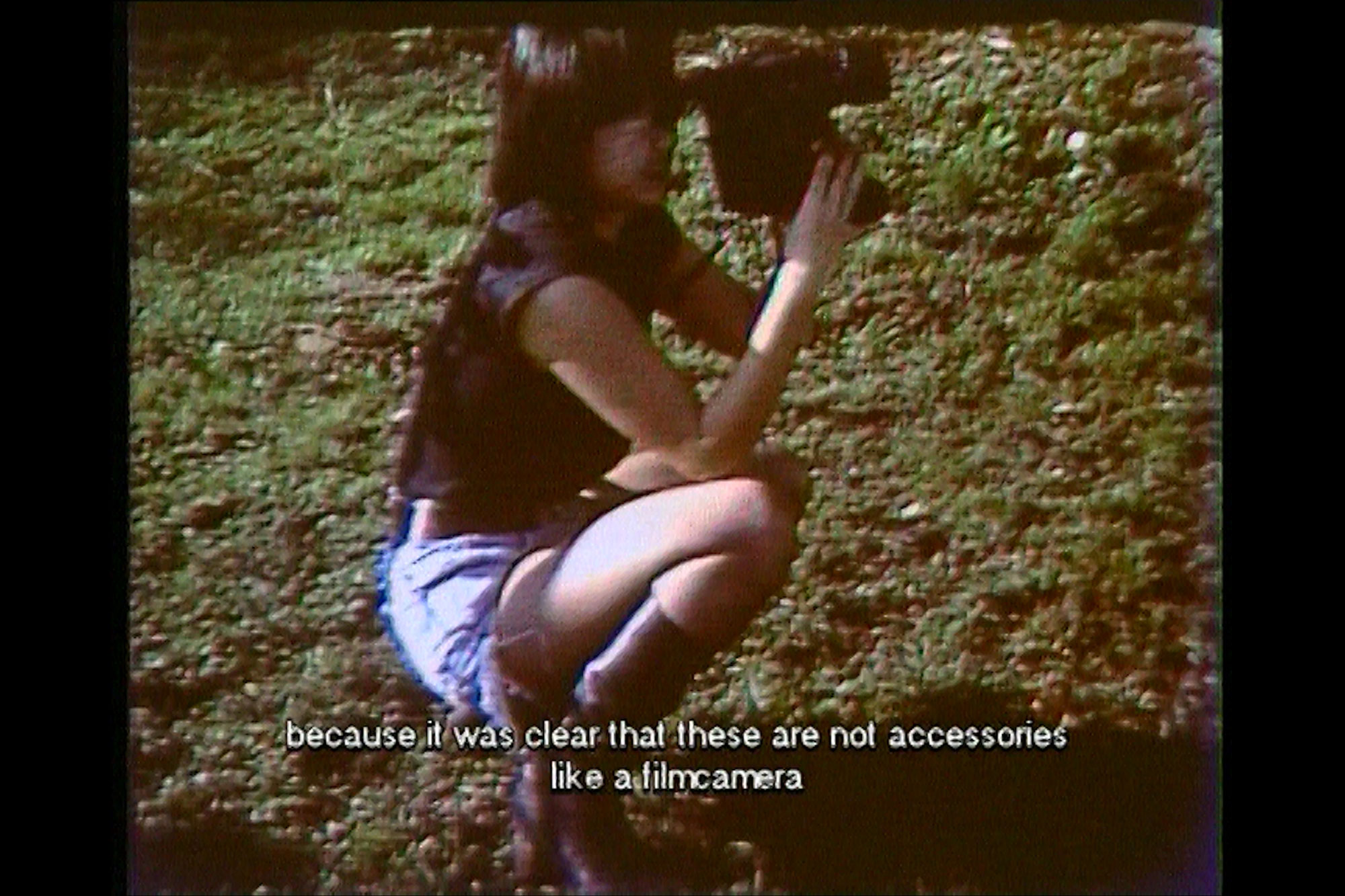 an asian woman squatting in the grass with a VHS camera.