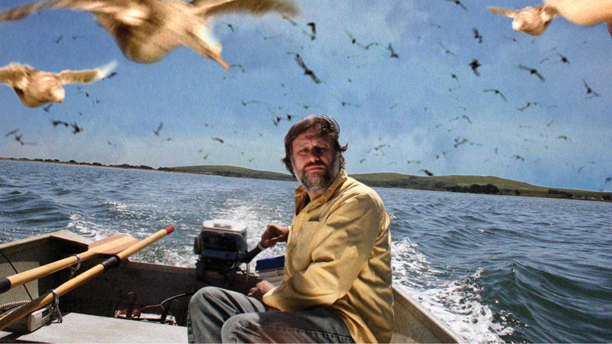 a man in a fishing boat on the ocean surrounded by gulls