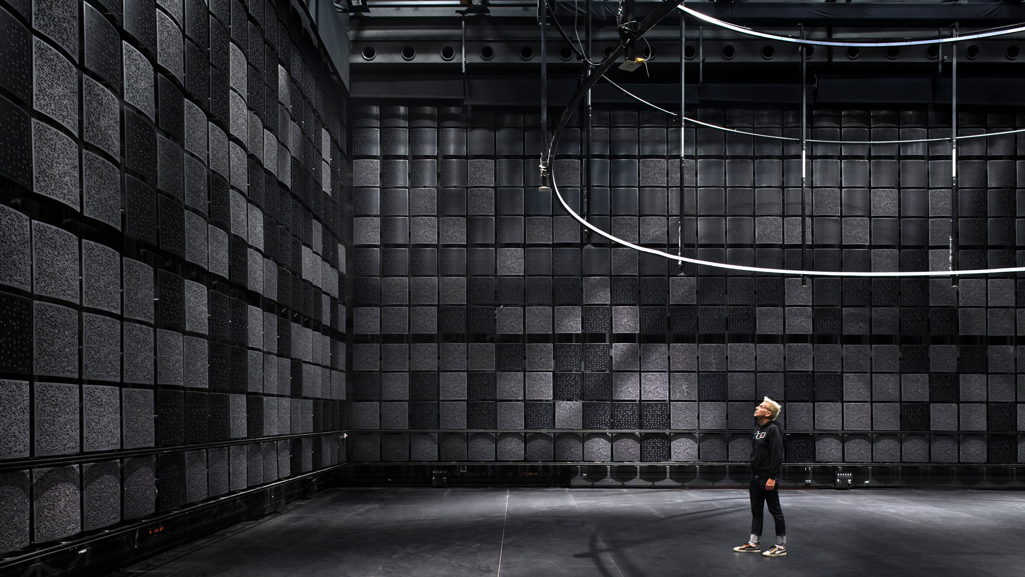 a man in a room full of black acoustic tiles with a rigging apparatus hanging above.