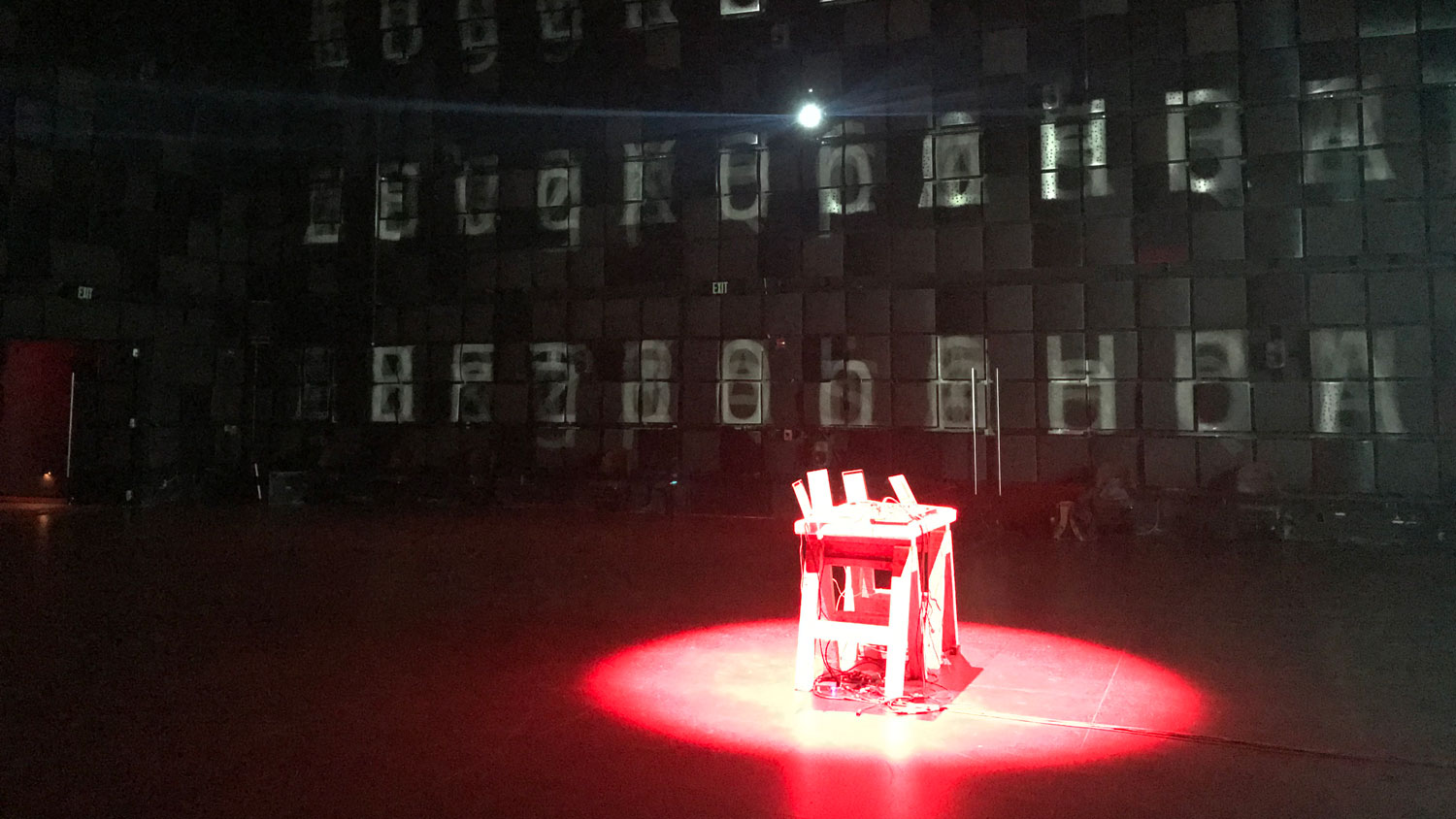 a table bathed in red with letters projected on the walls