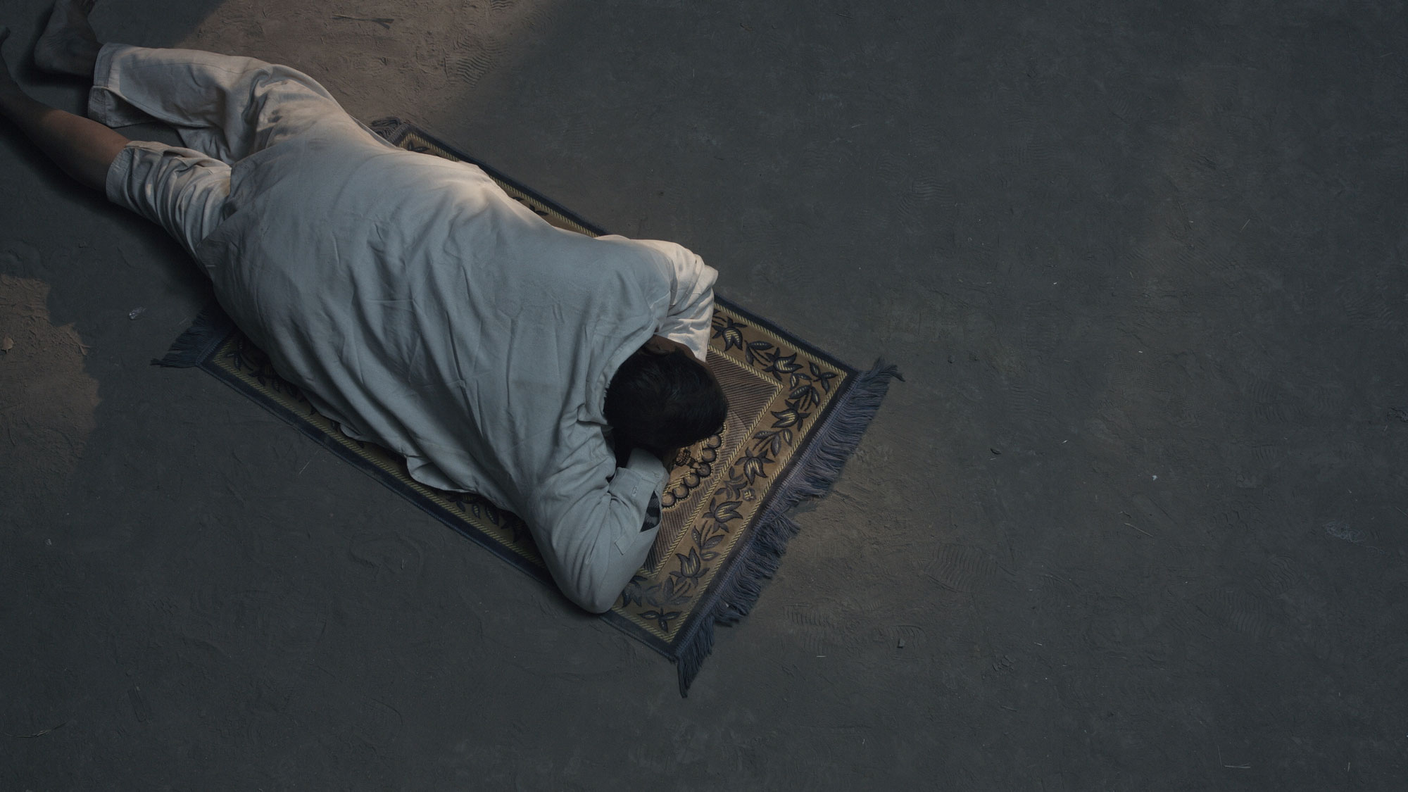 a man laying in prostrate on a grey carpet