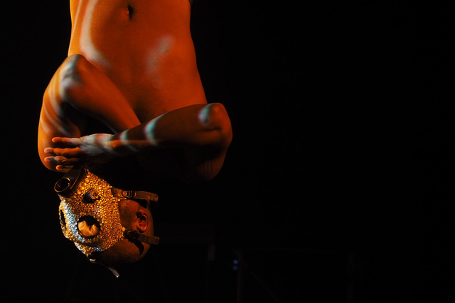 A shirtless african-american hangs upside down with a bejeweled mask on, arms crossed.