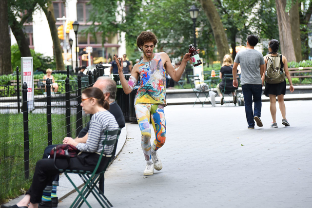 A black man in bright dancer tights strutting in a New York City park