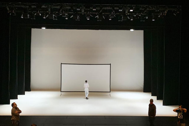 a person in white on stage against a white screen and backdrop.
