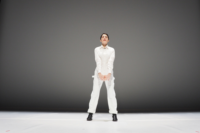 a single woman on stage in a white jumpsuit