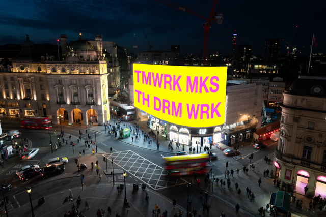 a large scale projection on a bright yellow screen in a town square reading TMWRK MKS