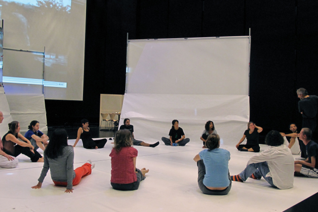 a group of dancers in studio 1 listening to a speaker.