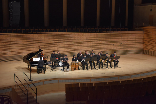 an orchestra on stage with a piano