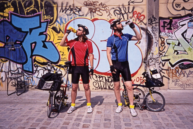two bicyclists drinking from their water bottles with a wall of graffiti in the background