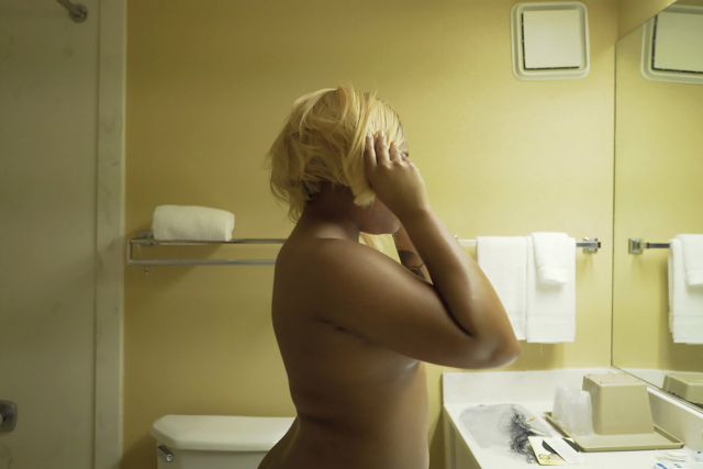 A nude African-American woman adjusts her blonde wig in a mirror.