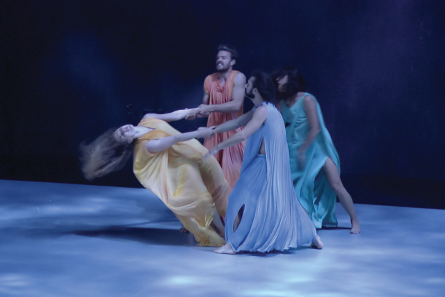 four dancers in multicolor robes in the theater