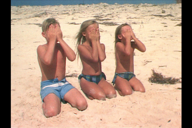 three childern kneeling in the sand with their hands over their faces