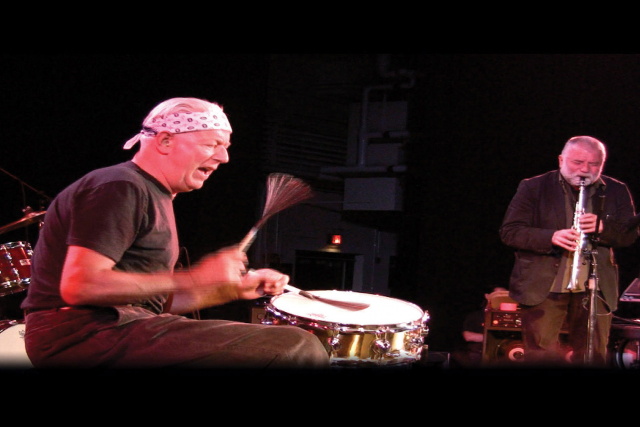 a man playing a drum set with a man playing soprano sax in the background