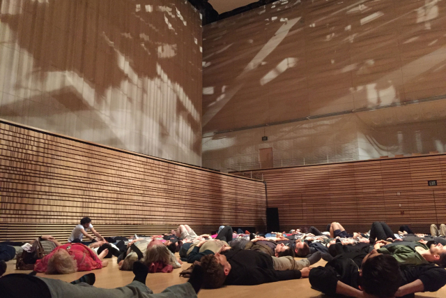 participants of Pauline Oliveros' Deep Listening practice laying across the Concert Hall stage at EMPAC in 2016.