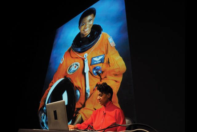 black women in orange flight suit in front of an image of an astronaut.