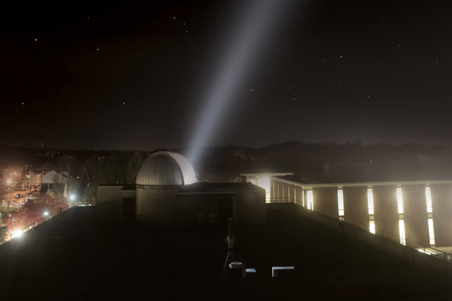 an observatory with a beam shining up at night