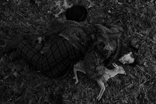 a man laying with a fawn on the ground