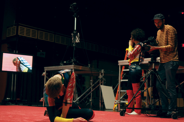 a dancer in the foreground on a red carpet being filmed while maria hassabi looks on at a video screen