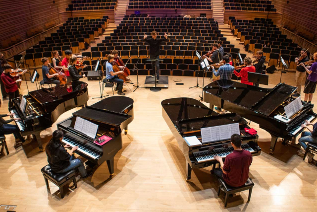 four pianos on the concert hall stage with players and a conductor