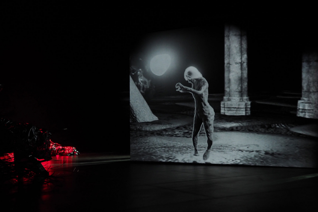 A screen in dark studio 1 shows a dancer in black and white