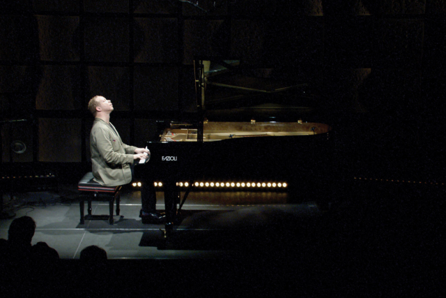a pianist at a black grand piano