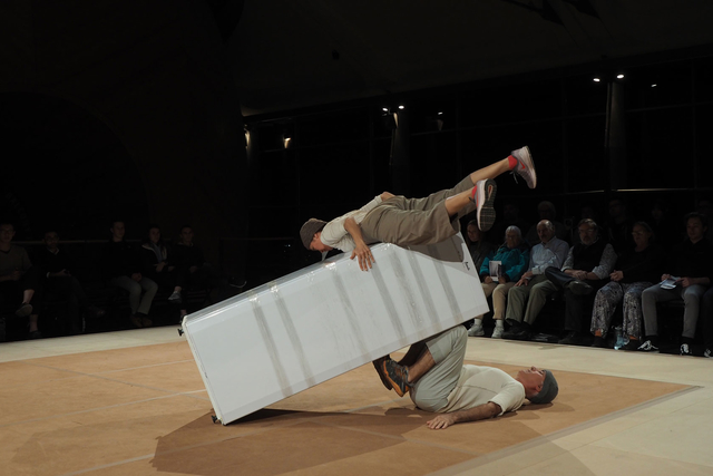 two people doing a headstand against a refridgerator on stage
