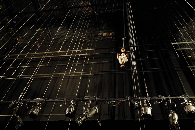 a dancer hanging like a gymnast 40' up among the theater fly tower line sets.