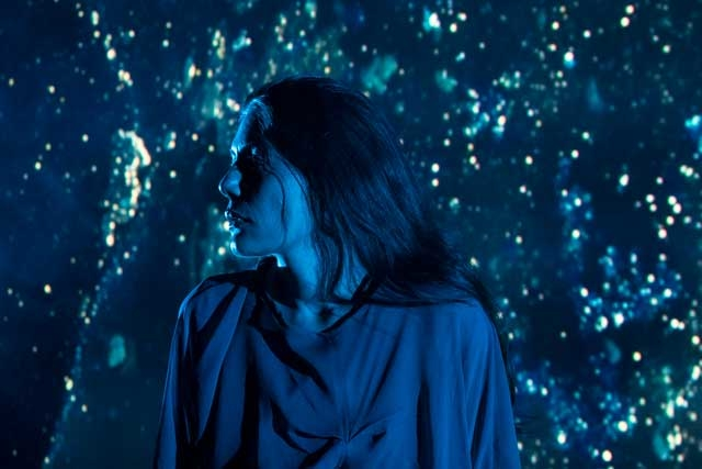 a iranian woman stands agains a background of star-like blue light.
